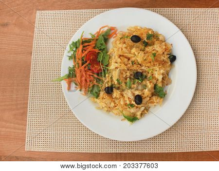 Bacalhau codfish dish made with dried and salted cod, boiled eggs, potato chips, olives. Served with carrot, tomatoes and greens salad. Traditional portuguese food on white plate at restaurant table.