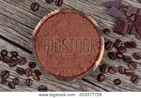 Cacao powder in a bowl with dark chocolate and coffee beans on wooden table