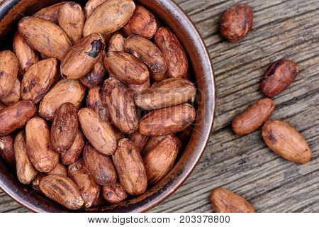 Bowl with cacao beans on wooden table