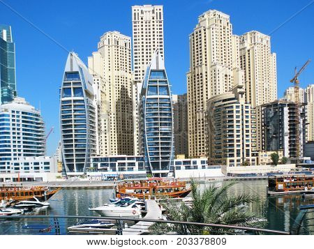 Beautiful buildings lit by the sun pleasure boats gliding over the watery surface in a new area of Arab of the city Dubai