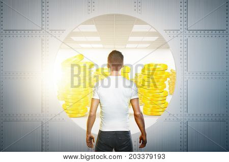 Back view of young businessman looking at open bank vault with golden coins. Success and finance concept. 3D Rendering