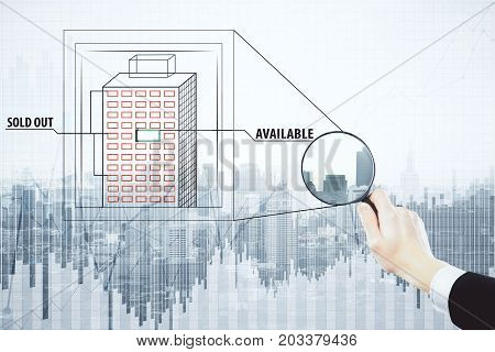 Businessman hand using magnifier to look at building with sold out and available flats on abstract city and business chart background. Real estate concept. Double exposure