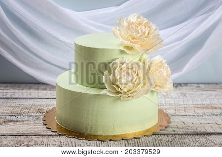Beautiful Home Made Wedding Two-tiered Cake Decorated With Beige Roses.