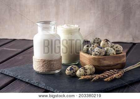 Eco Farm Products Milk, Sour Cream, Yogurt, Eggs On Dark Wooden Background. Concept Of Home Made Nat