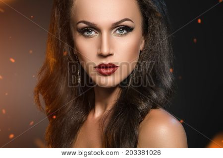 woman standing in the sparks of fire. Beauty portrait of brunette in black earrings on a dark background with the flying sparks from the fire