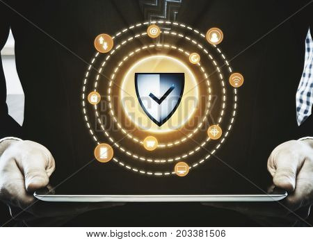 Businessman using tablet with abstract antivirus shield. Cyberspace safety concept. Close up