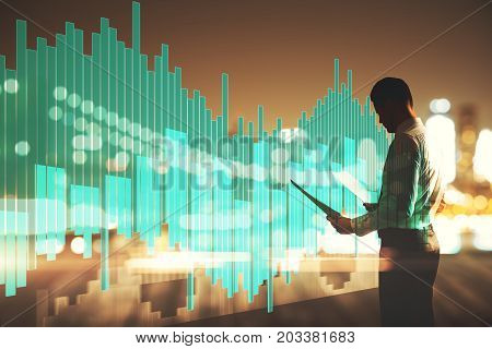 Side view of young businessman holding document on abstract night city background with abstract digital business chart hologram. Analytics concept. Double exposure