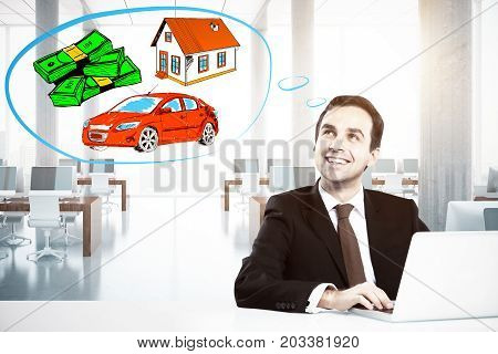 Happy young businessman in modern office using laptop and daydreaming about wealth. Wealthy concept