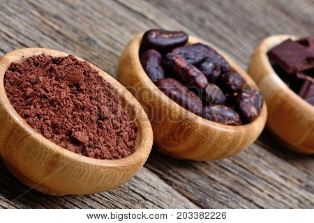 Cacao powder beans and dark chocolate in a bowls on table