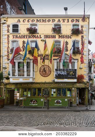 Dublin Ireland - August 7 2017: Historic Oliver St. John Gogarty pub on the corner of Temple bar and Bedford Row has yellow facade and displays many flags and U2 poster. Street scene.