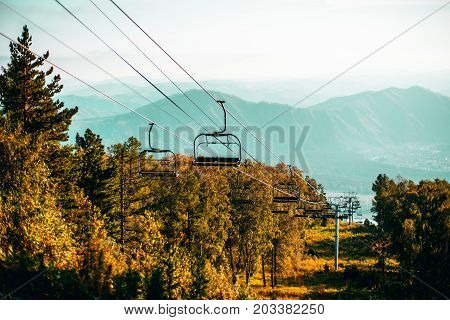 Mountain cableway stretching down over autumn meadows with native grasses pine cedar and birch trees hill ridge and settlement in hazy teal background Altai mountains Manzherok district Russia