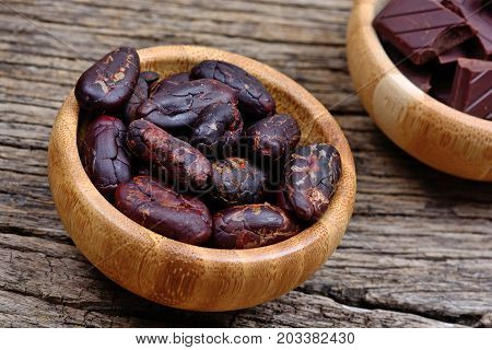 Cacao beans with dark chocolate in a bamboo bowls on table
