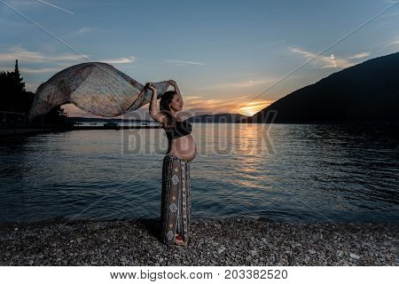 Pregnant woman holding scurf in the sunset