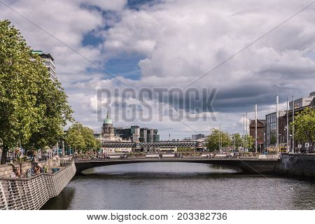 Dublin Ireland - August 7 2017: Looking east off O-Connell Bridge over Liffey River. Facades along the water people over bridge heavy cloudscape some green trees and dome of the Custom House.