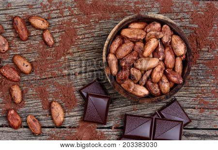 Cacao beans with dark chocolate on wooden table