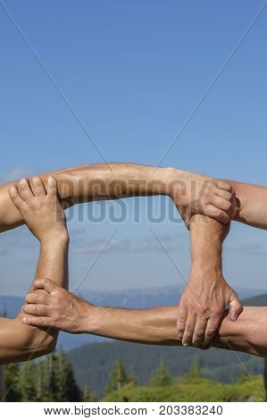 Successful team: hands holding together on nature background close up