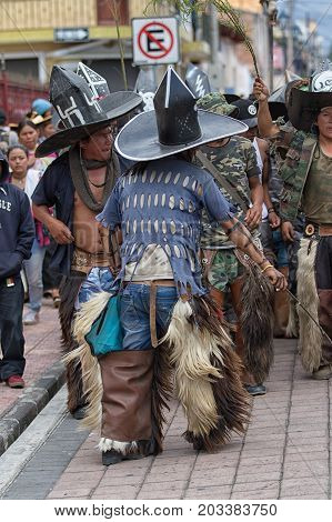 June 29 2017 Cotacachi Ecuador: kichwa indigenous people with extra large hats and chaps dancing on the street during Inti Raymi festival