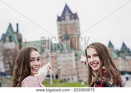 A Quebec City scape with Chateau Frontenac and young teens enjoying the view.