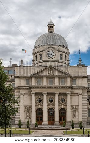 Dublin Ireland - August 7 2017: Closeup of Historic beige Government Building in Merrion Street Upper with gray dome and clock under blue sky with white clouds. Statues in facade and Irish flag