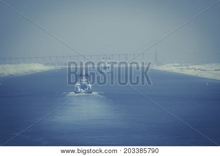 In the Suez Canal - a military ship and a tugboat forward to the city of El Qantara and the Mubarak Peace Bridge in foggy evening mood
