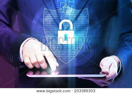 Abstract image of businessman using digital tablet with padlock hologram on dark background. Antivirus concept