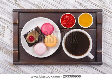 Cup of coffee honey strawberry jam piece chocolate cake with cherry and macaron cakes on tray on white wooden table. Lifestyle concept. Close up