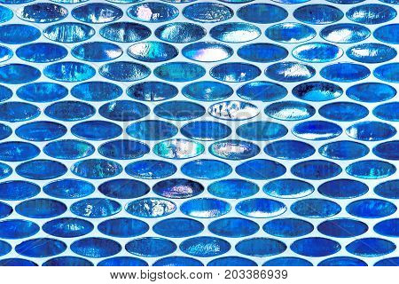 Pattern and structure in blue and white shades mades from small oval slightly shining tile ornaments