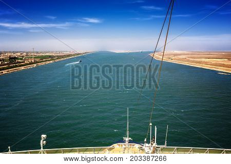 The Suez Canal at Port Said with the 2 exits to the Mediterranean Sea in the foreground a ship's bow with rail