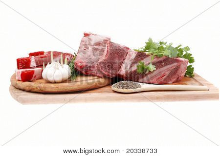 raw meat : fresh beef pork big rib and fillet with garlic and green stuff on wood isolated over white background