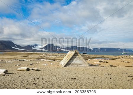 Driftwood cabin at the beach at Svalbard with driftwood and walrus bones lyingin the sand. Blue sky and white clouds, ocean, beach and mountains