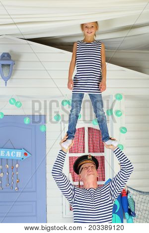 MOSCOW - OCT 04, 2016: Father (with model release) in cap with the inscription Pacific Fleet with daughter (with model release) in vests perform acrobatic support at arms in front of the white house
