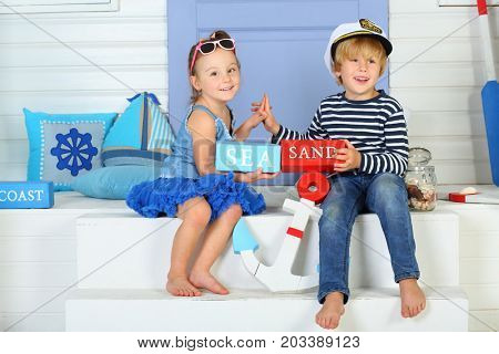 MOSCOW - OCT 04, 2016: Happy boy (with model release) in hat with inscription admiral and striped vest with girl (with model release) holding bars labeled sea and sand sitting on porch