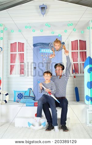 MOSCOW - OCT 04, 2016: Father (with model release) in cap  with daughter (with model release) perform acrobatic support at arms with son (with model release) on his lap on porch