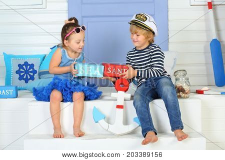 MOSCOW - OCT 04, 2016: A boy (with model release) in cap with inscription Admiral and little girl (with model release) in sunglasses with bars labeled sea and sand sitting on porch in front of door