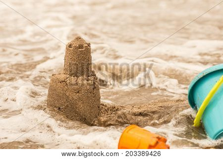 Persistent Tower Of The Sand Castle Washes Away In The Sea Water.