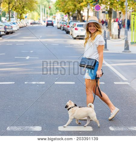 Young Woman Crosses A City Street Wit A Pug