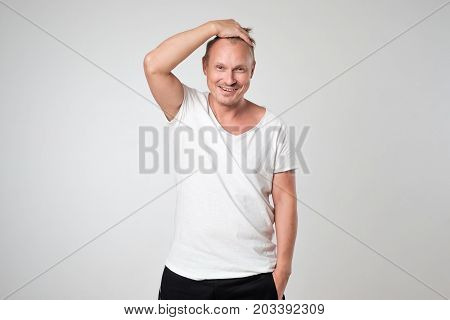 Smiling young man in white t-shirt standing against white background Concept of self confident man. Positive man emotion