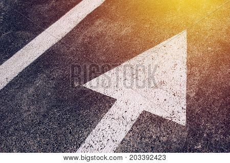 Moving in the right direction white arrow symbol as traffic sign on asphalt road for motion directing toward the successful future represented by the bright sunlight
