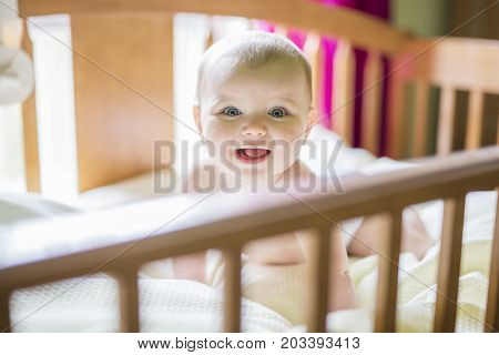 A Close-up portrait of a cheerful cute baby in the crib at home