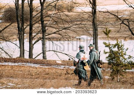 Rogachev, Belarus - February 25, 2017: Two Unidentified Re-enactors Dressed As German Wehrmacht Infantry Soldiers In World War II Marching Along Forest Road At Autumn Season.