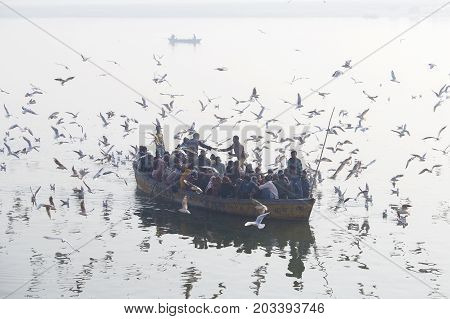 VARANASI INDIA - JANUARY 25 2017 : Unknown indian people are in a wooden boat that sailed on the Ganges River morning in Varanasi. Uttar Pradesh India