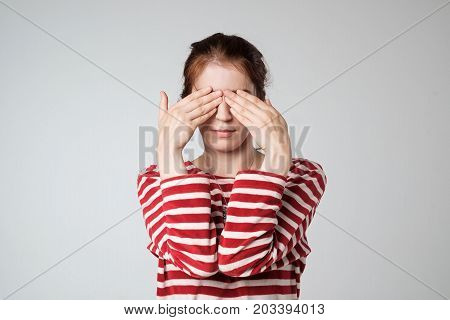 Young woman covering face with hands on gray background. Concept of shy embarrassment emotion expression