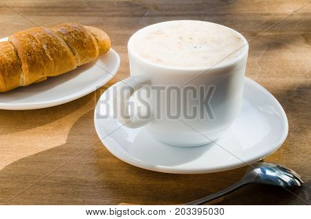 Cappuccino or coffee latte with foam in white cup and croissant on wooden table.