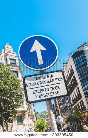 Ahead Only Sign With A Sign Where It Is Written In Catalan And Spanish - Except Taxis And Bicycles