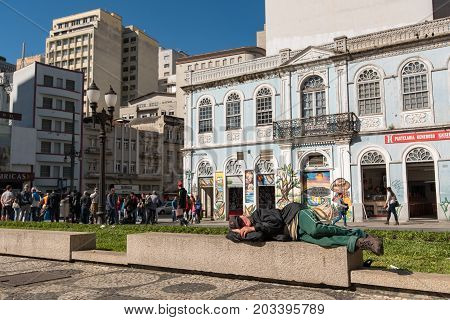 Curitiba, Brazil - July 21, 2017: Homeless man sleeping on the concrete bench in the square of Curitiba old town.