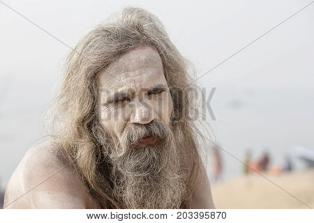 VARANASI INDIA - JANUARY 26 2017 : Portrait of Shaiva sadhu holy man on the ghats of the Ganges river in Varanasi India . Close up