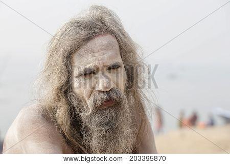 VARANASI INDIA - JANUARY 26 2017 : Portrait of Shaiva sadhu holy man on the ghats of the Ganges river in Varanasi India . Close up