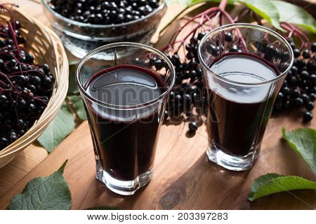 Two glasses of elderberry syrup on a wooden table with elderberries in the background