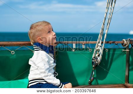 Joyful young captain portrait. Happy child on deck of sailing yacht have fun discovering islands in tropical sea on summer coastal cruise. Travel adventure yachting with kids on family vacation.