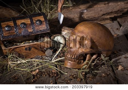 Human skull and treasure chest on weathered wood surface